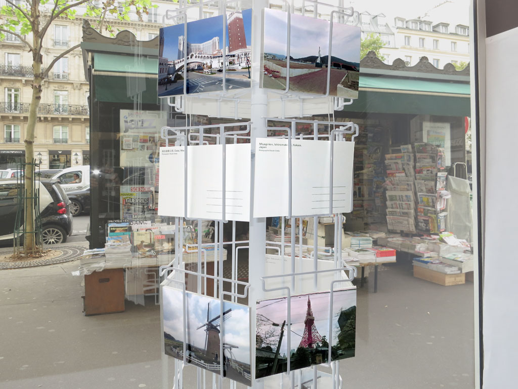Claude Closky, '5 continents', 2012, five windows, five postcard stands 170 x 30 x 30 cm, postcards, offset print on 350 g. card 10,5 x 15 cm. Exhibition view 'L'écriture est un voyage', windows @ 170 Boulevard Saint-Germain, Paris. 18 October 2012 - 2 January 2013. Curated by Hervé Mikaeloff
